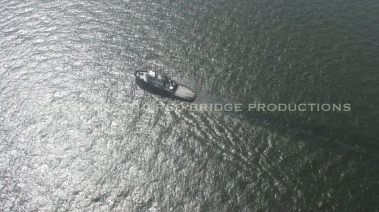 A boat near the spill site kicks up a dark oily substance in its wake