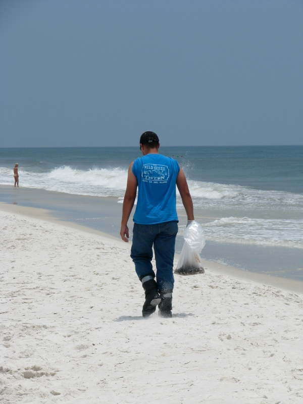 A cleanup worker clears oil debris in Pensacola, Fl