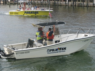 BP employed cleanup workers return to Destin Harbor alongside a tourist-filled parasailing boat.
