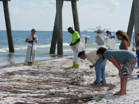 Cleanup workers stand behind onlookers at Pensacola Beach on June 23rd